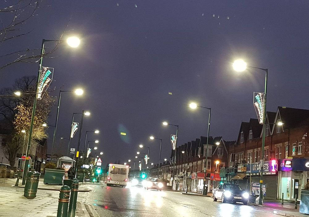 cars driving through acocks green high street at night time