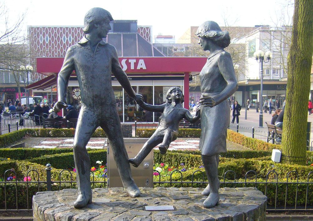 statue of a man and women holding a child